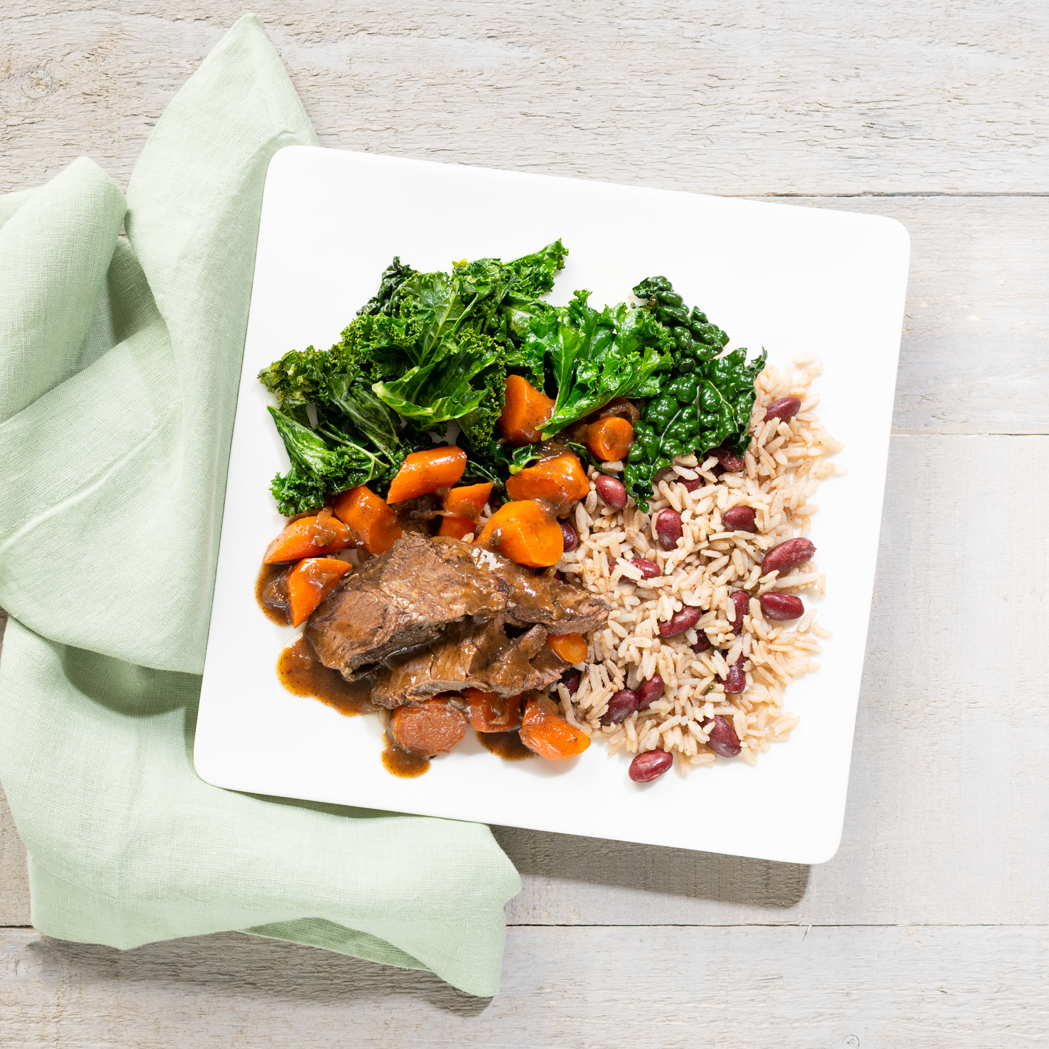 Slow cooker jerk beef pot roast with braised carrots, rice and peas & wilted greens